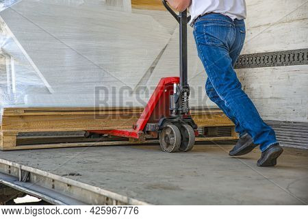 Manual Loader. A Forklift Is Towing A Hand Pallet Truck. Folds And Straightens The Load In The Truck