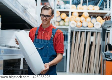 Salesman With A Roll Of Insulation In His Hands Standing In A Hardware Store.