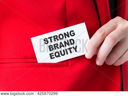 Woman Putting A Card With Text Strong Brand Equity In The Pocket, Hand Close-up
