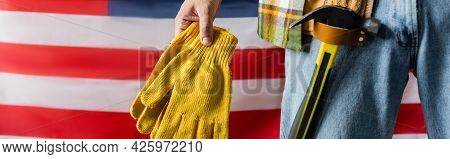 Cropped View Of Workman With Hammer In Tool Belt Holding Work Gloves Near Usa Flag, Labor Day Concep