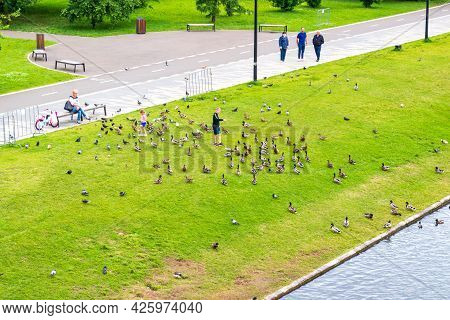 Krasnoyarsk, Russia - June 28, 2021: Children Feed A Flock Of Ducks On The Waterfront. Comfortable W