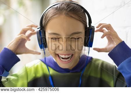 A Ten-year-old Girl Listens To Loud Music Through Headphones. She Sings Along And Wrinkles Her Nose
