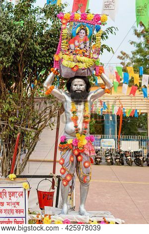 A Unidentified Man Painted His Body With Silver Colour And Holding A Picture Of Lord Krishna Posed A