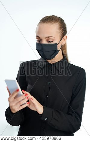 Woman In Face Mask Using Smartphone Isolated On White Studio Background
