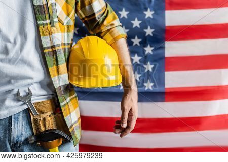 Cropped View Of Workman In Plaid Shirt And Tool Belt Holding Hardhat Near Blurred Usa Flag, Labor Da