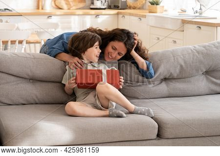 Cheerful Boy Of 5 Sit On Couch Holding Wrapped Box With Gift From Loving Single Mother. Kid Son Cele