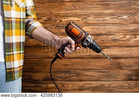 Cropped View Of Workman With Electric Drill Near Wooden Wall, Labor Day Concept