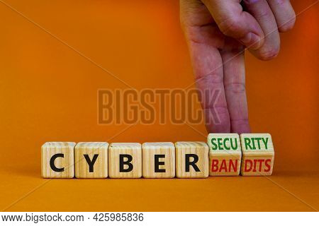 Cyber-security Vs Cyber-bandits Symbol. Businessman Turns Wooden Cubes, Changes Words Cyber-bandits