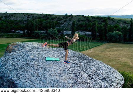 Young Woman Doing Yoga Fitness Exercise In The Mountains. The Concept Of Yoga, Fitness, Meditation,