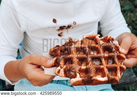 Children's Hands Holding A Belgian Waffle With Chocolate Topping. Close Up
