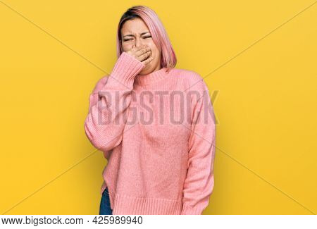 Hispanic woman with pink hair wearing casual winter sweater smelling something stinky and disgusting, intolerable smell, holding breath with fingers on nose. bad smell
