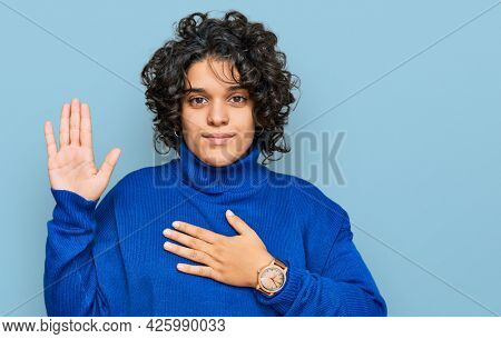 Young hispanic woman with curly hair wearing turtleneck sweater swearing with hand on chest and open palm, making a loyalty promise oath