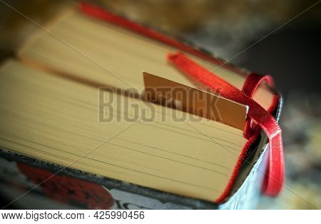 An Unrecognized Random Book Close Up With Silk Thread Bookmark Along With A Paper Card In The Middle