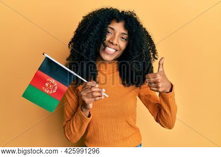 African american woman with afro hair holding afghanistan flag smiling happy and positive, thumb up doing excellent and approval sign