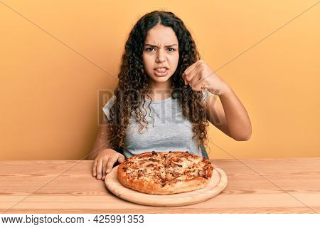 Teenager hispanic girl eating italian pizza annoyed and frustrated shouting with anger, yelling crazy with anger and hand raised
