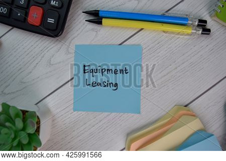 Equipment Leasing Write On Sticky Notes Isolated On Wooden Table.