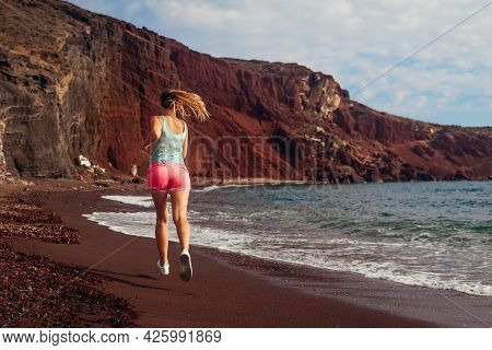 Woman Running On Red Beach On Santorini Island. Female Runner Jogging During Outdoor Workout On Seas