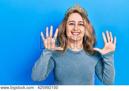 Middle age caucasian woman wearing queen crown showing and pointing up with fingers number ten while smiling confident and happy.
