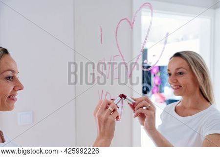 Woman Making Heart Shape And Inscription On The Mirror With Lipstick.