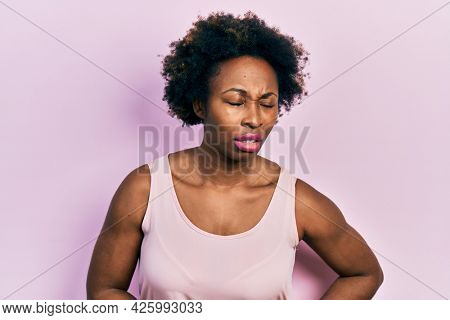 Young african american woman wearing casual sleeveless t shirt with hand on stomach because indigestion, painful illness feeling unwell. ache concept.