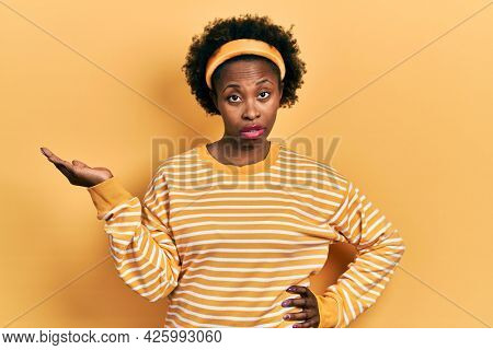 Young african american woman presenting with open palms, holding something in shock face, looking skeptical and sarcastic, surprised with open mouth