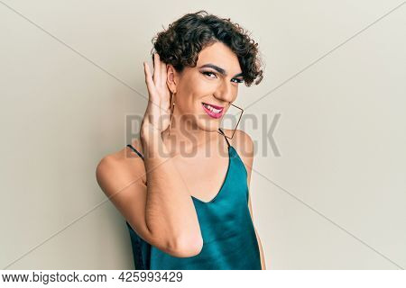 Young man wearing woman make up wearing party clothes smiling with hand over ear listening and hearing to rumor or gossip. deafness concept.