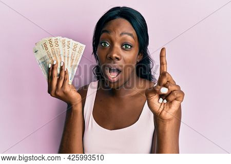 Young african american woman holding swedish krona banknotes smiling with an idea or question pointing finger with happy face, number one