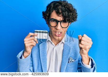 Hispanic young man holding credit card annoyed and frustrated shouting with anger, yelling crazy with anger and hand raised