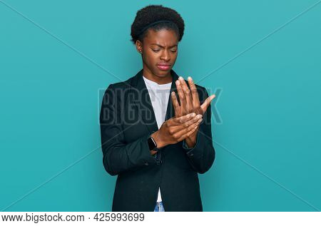 Young african american girl wearing business clothes suffering pain on hands and fingers, arthritis inflammation