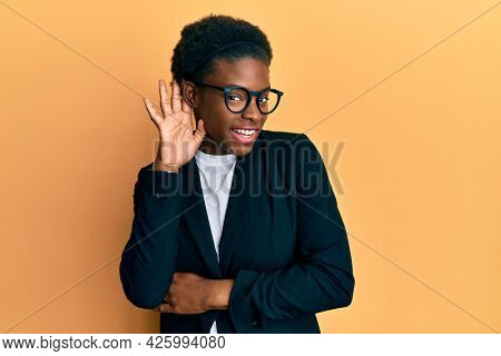 Young african american girl wearing business jacket and glasses smiling with hand over ear listening and hearing to rumor or gossip. deafness concept.