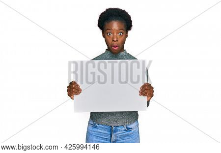 Young african american girl holding blank empty banner scared and amazed with open mouth for surprise, disbelief face