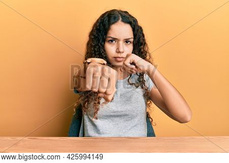 Teenager hispanic girl wearing casual clothes sitting on the table punching fist to fight, aggressive and angry attack, threat and violence