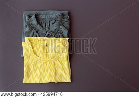 Two Womens Blouses In Yellow And Gray Are Neatly Folded On A Dark Gray Background On The Left, Copy