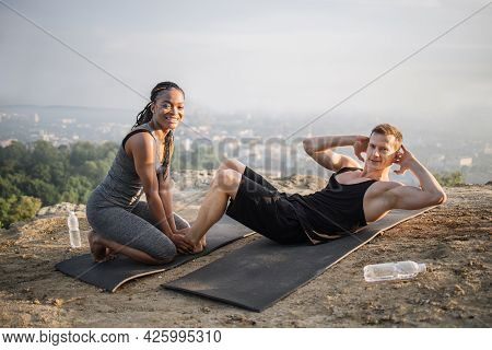 Strong Caucasian Man Doing Abdominal Crunches On Yoga Mat While African Woman Holding His Bare Feet.