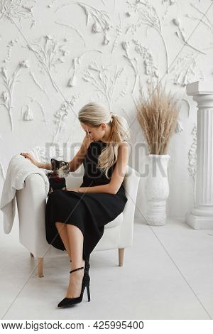 A Young Woman In A Black Dress And Black Shoes Sits With Cute Little Dog In A Vintage Armchair. Mode