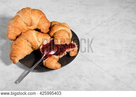 Fresh French Croissant With Cherry Jam On Grey Plate On Gray Background, One Teaspoon Spreads Jam On
