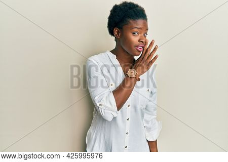 Young african american girl wearing casual clothes hand on mouth telling secret rumor, whispering malicious talk conversation