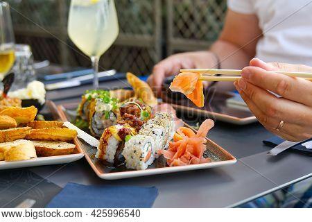 Man Eating Salmon Sashimi In Japanese Restoran. Man Holding Chopsticks Eating Fresh Salmon Sashimi