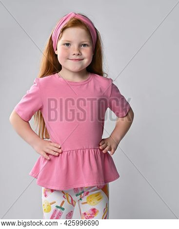 Friendly Smiling Little Red-haired Girl Wearing Summer Fashion Clothes, Looking At The Camera. Adora