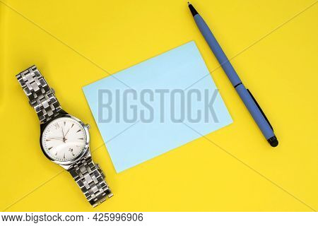 On A Yellow Background Among A Pen And A Wristwatch There Is A Blue Sheet For Notes.