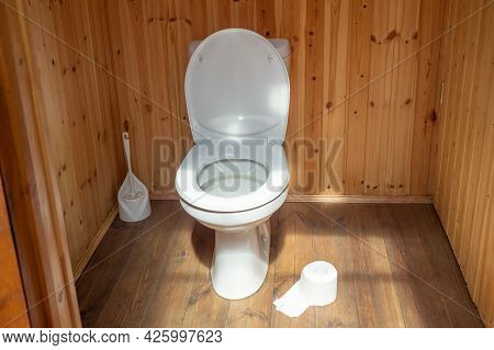 A White Toilet With A Plastic Lid In A Wooden Outdoor Toilet. A Plastic Brush In The Background. A R
