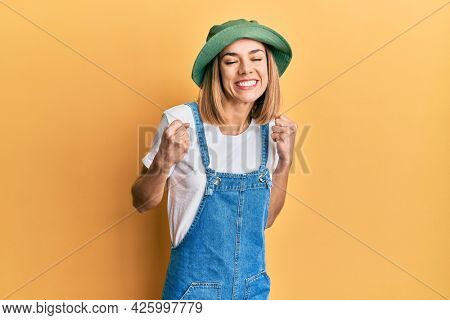 Young caucasian blonde woman wearing denim jumpsuit and hat with 90s style excited for success with arms raised and eyes closed celebrating victory smiling. winner concept.