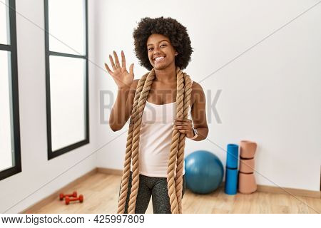 Young african american woman with afro hair at the gym training with battle ropes waiving saying hello happy and smiling, friendly welcome gesture