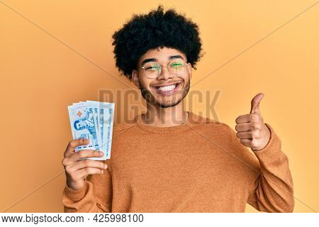 Young african american man with afro hair holding 50 thai baht banknotes smiling happy and positive, thumb up doing excellent and approval sign