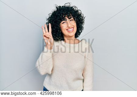 Young middle east woman wearing casual white tshirt showing and pointing up with fingers number three while smiling confident and happy.