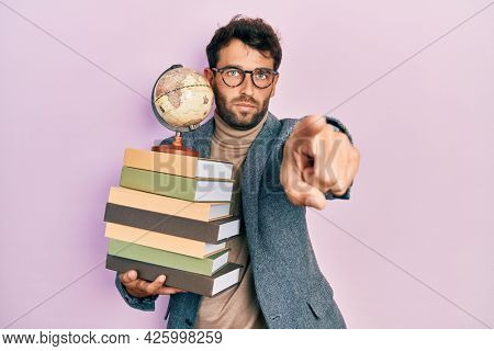 Handsome man with beard geography teacher pointing with finger to the camera and to you, confident gesture looking serious