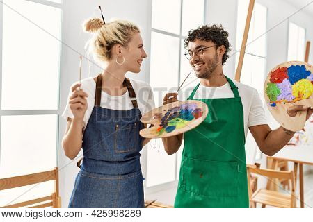 Young artist couple smiling happy holding paintbrush and palette at art studio.