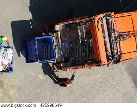 Garbage Removal. The Scavengers Are Rolling The Trash Can To The Garbage Truck, Top View. Garbage Lo