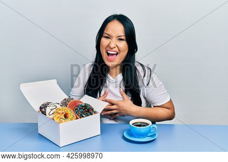 Beautiful hispanic woman with nose piercing eating doughnuts and drinking a cup of coffee smiling and laughing hard out loud because funny crazy joke.