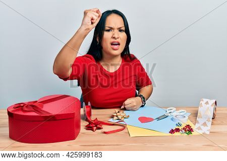 Beautiful hispanic woman with nose piercing doing handcraft creative decoration angry and mad raising fist frustrated and furious while shouting with anger. rage and aggressive concept.